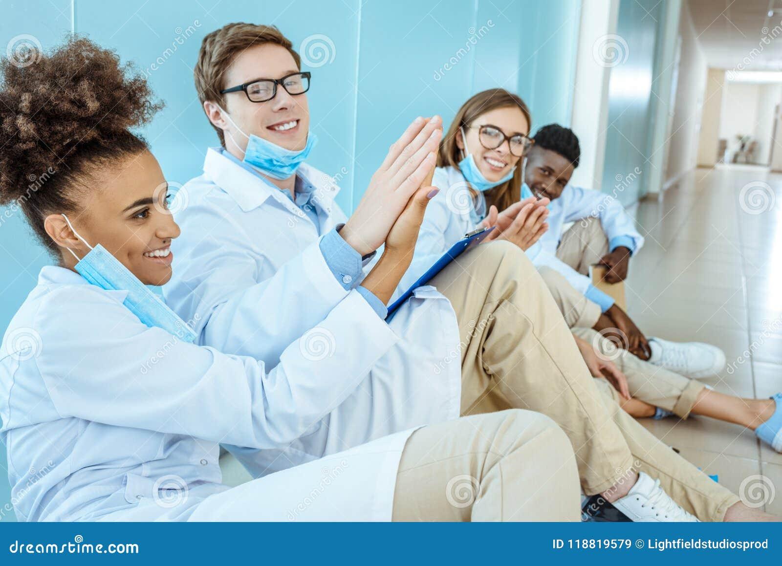 Vier glimlachende jonge medische internen die in witte robes op een vloer zitten
