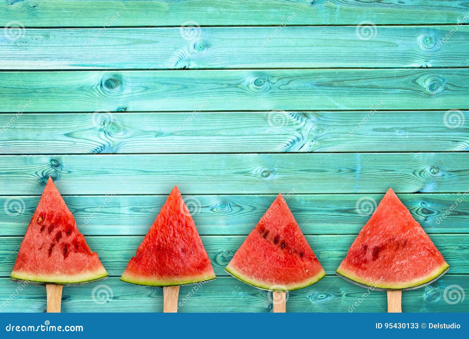 Vier ijslollys van de watermeloenplak op blauwe houten achtergrond met exemplaarruimte, het concept van het de zomerfruit