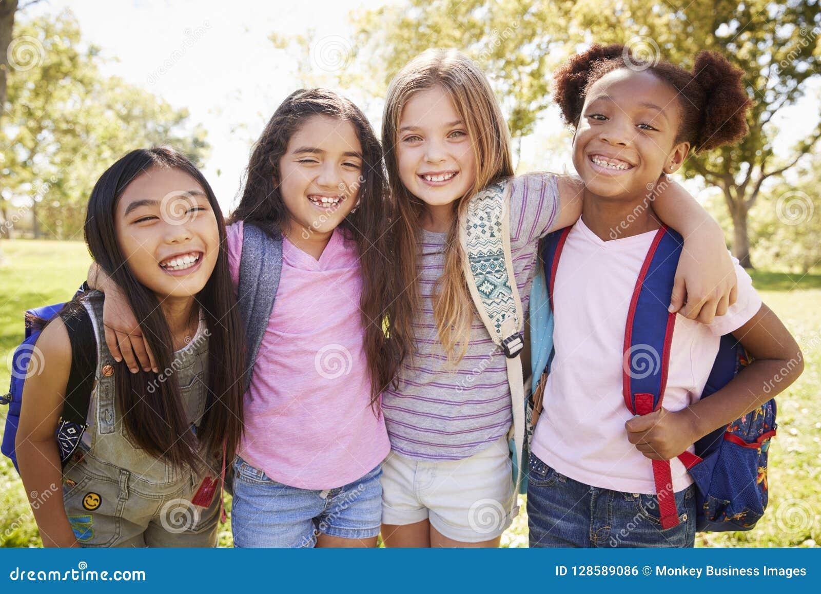 Vier jonge glimlachende schoolmeisjes op een schoolreis