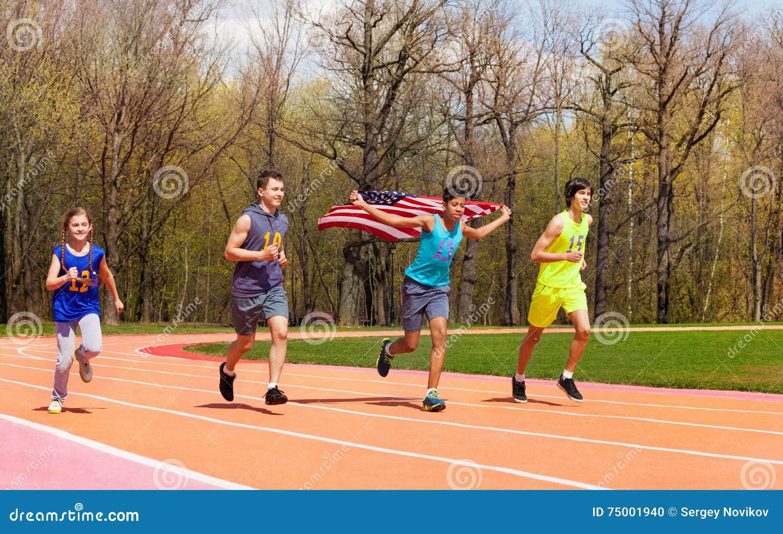 Vier jonge sprinters die Amerikaanse vlag op spoor golven