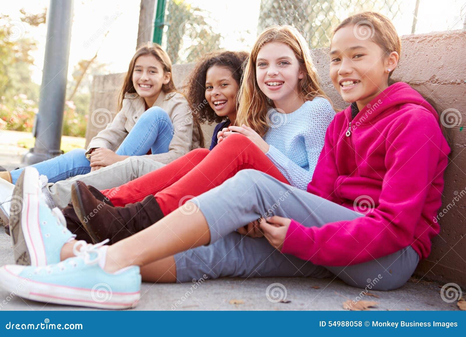 Vier junge Mädchen, die heraus zusammen im Park hängen