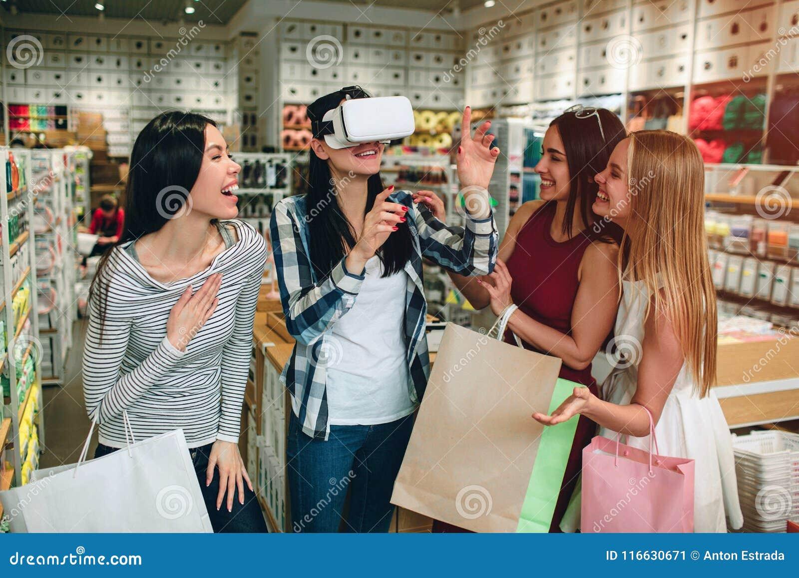 Vier Mädchen haben etwas Spaß Brunette im Hemd hat VR-Gläser auf ihrem Gesicht und dem Halten ihrer Hände in der Luft während sie