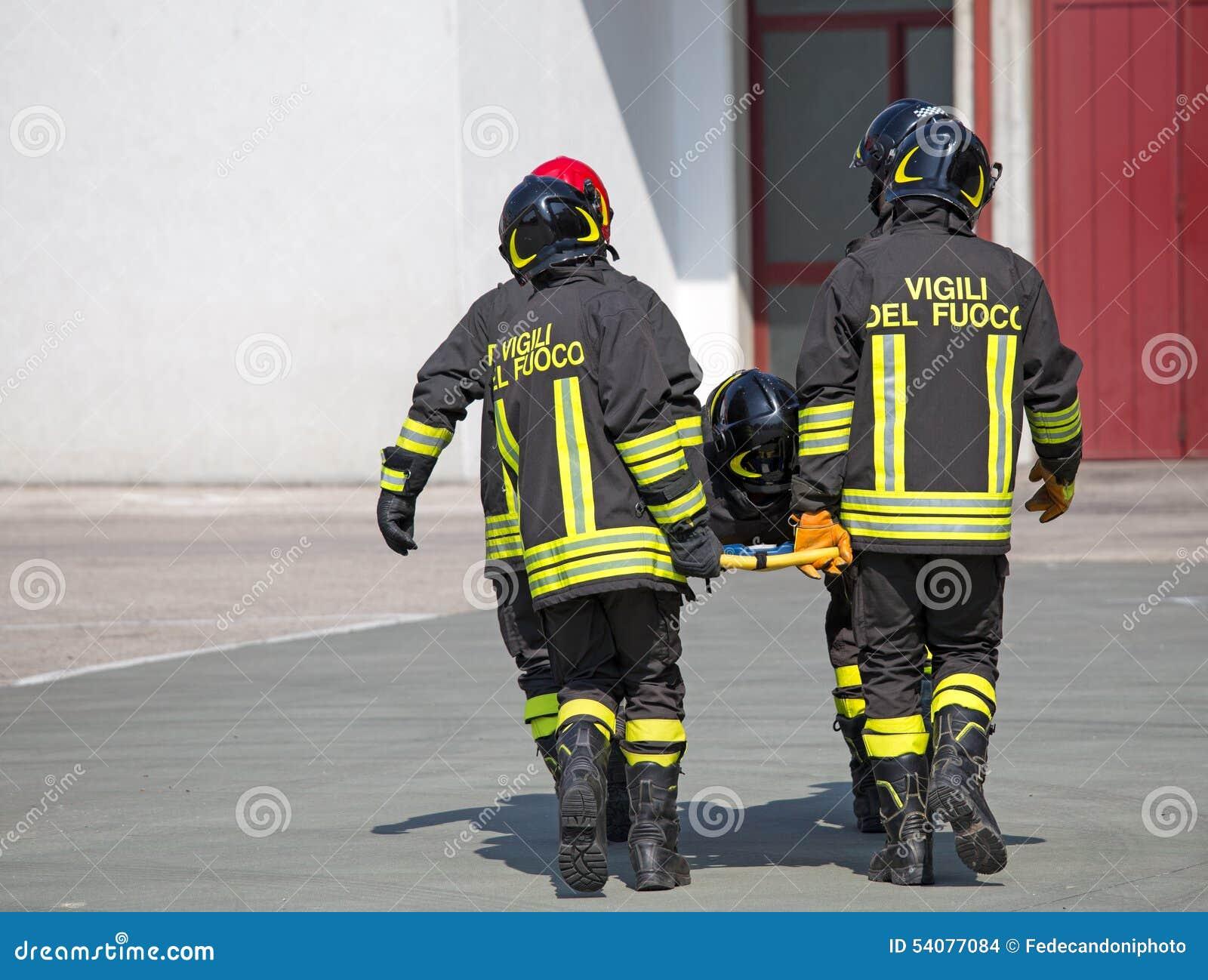 Vier moedige Brandbestrijders vervoeren een medebrandbestrijder