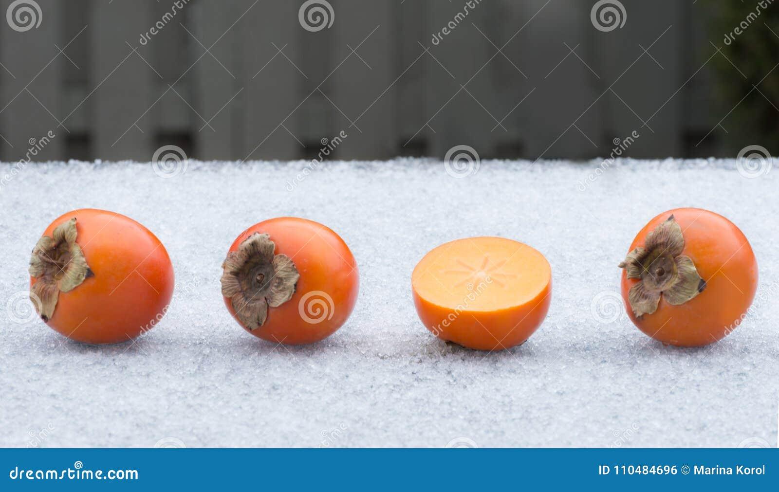 Vier Persimonen auf Eis Hälfte der Frucht und drei ganzer Persimonen