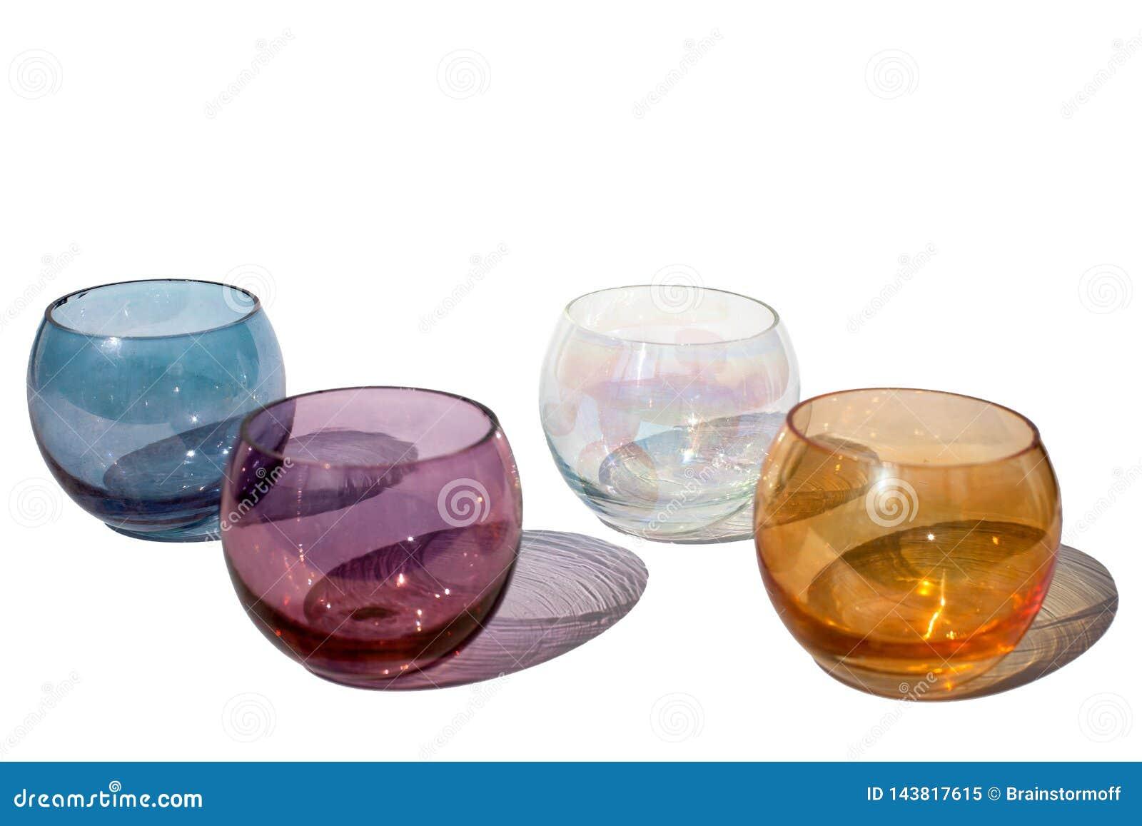 Vier runde Gläser der mehrfarbigen Weinlese auf einem weißen Hintergrund mit schönen farbigen Schatten lokalisierten im Sonnenlic
