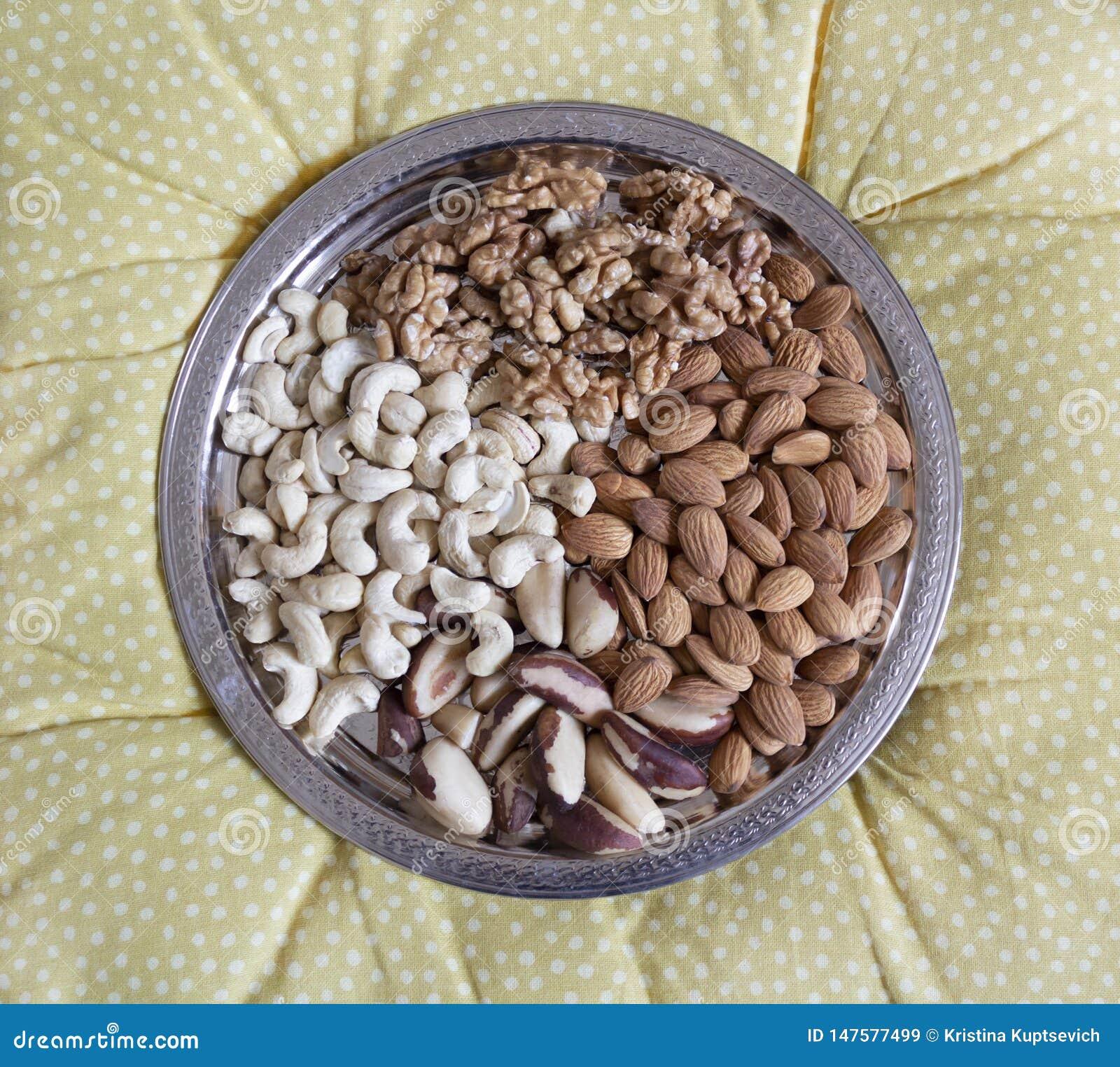 Vier soorten gepelde noten op een zilveren dienblad Okkernoten, cachou, paranoten, amandelen