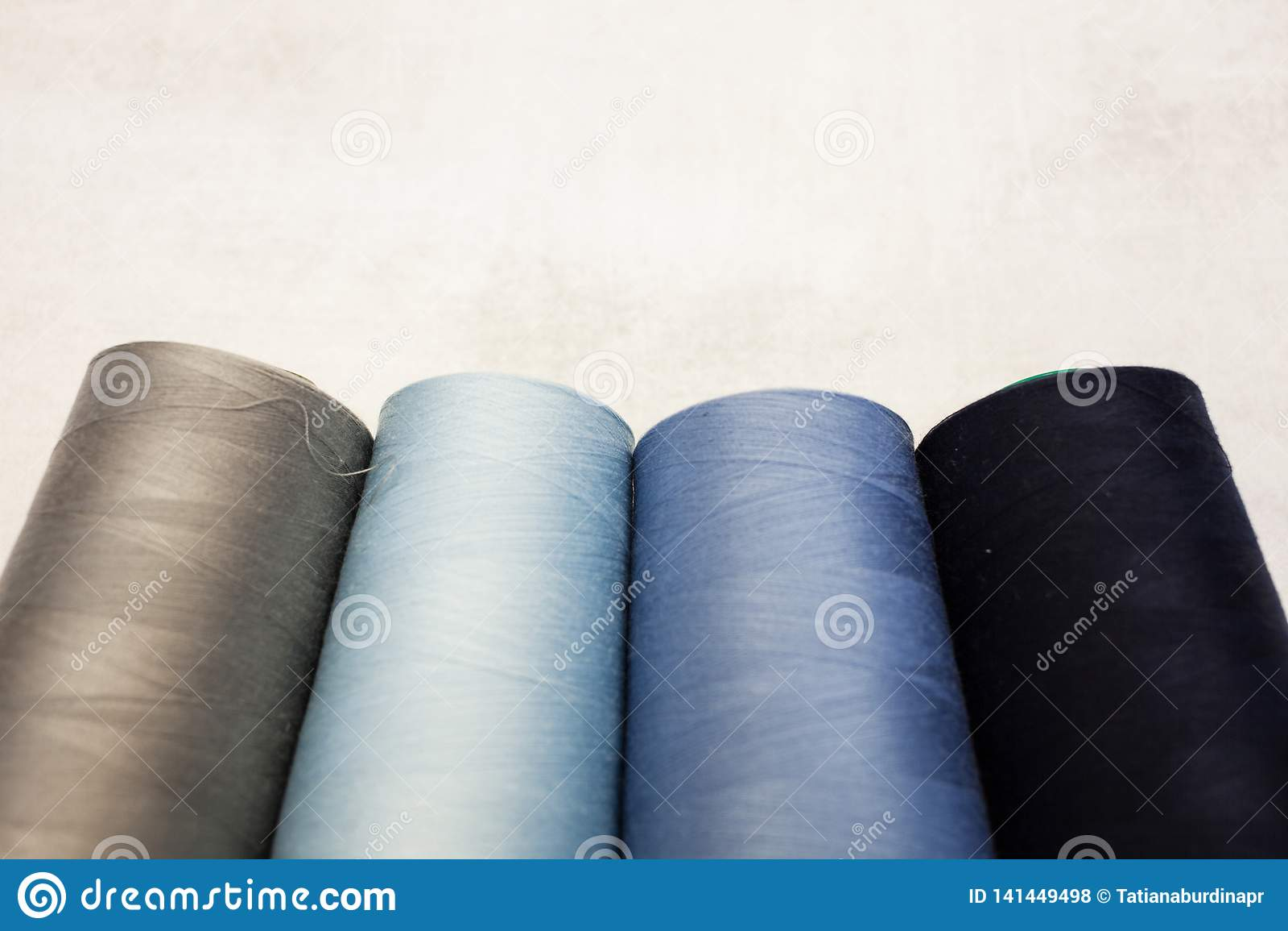Vier Spulen von kalten Farben: grau, blau und hellblau Nähende Produktion und Haupthandwerk
