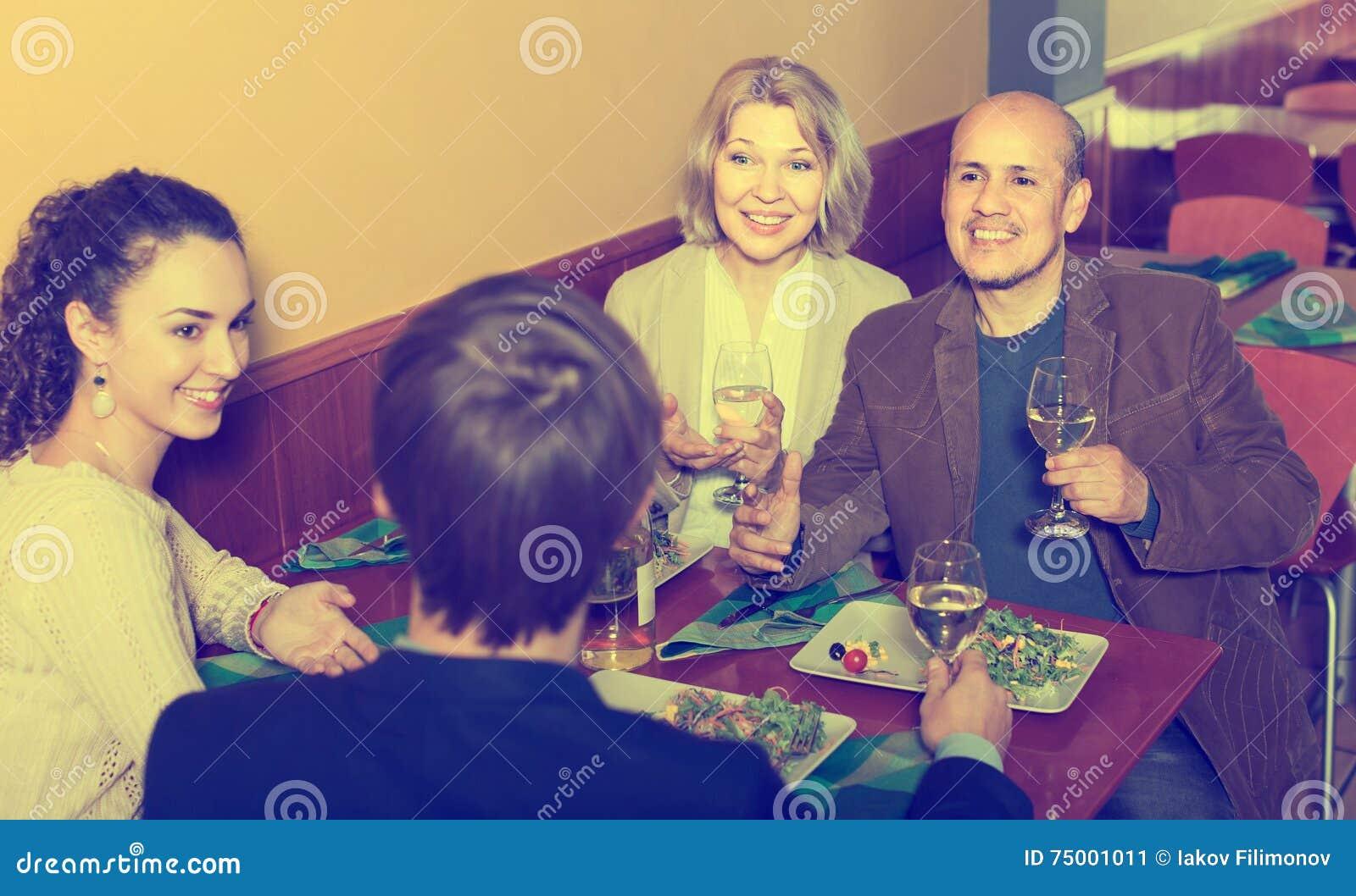 Vier volwassenen die met wijn en diner in restaurant lachen