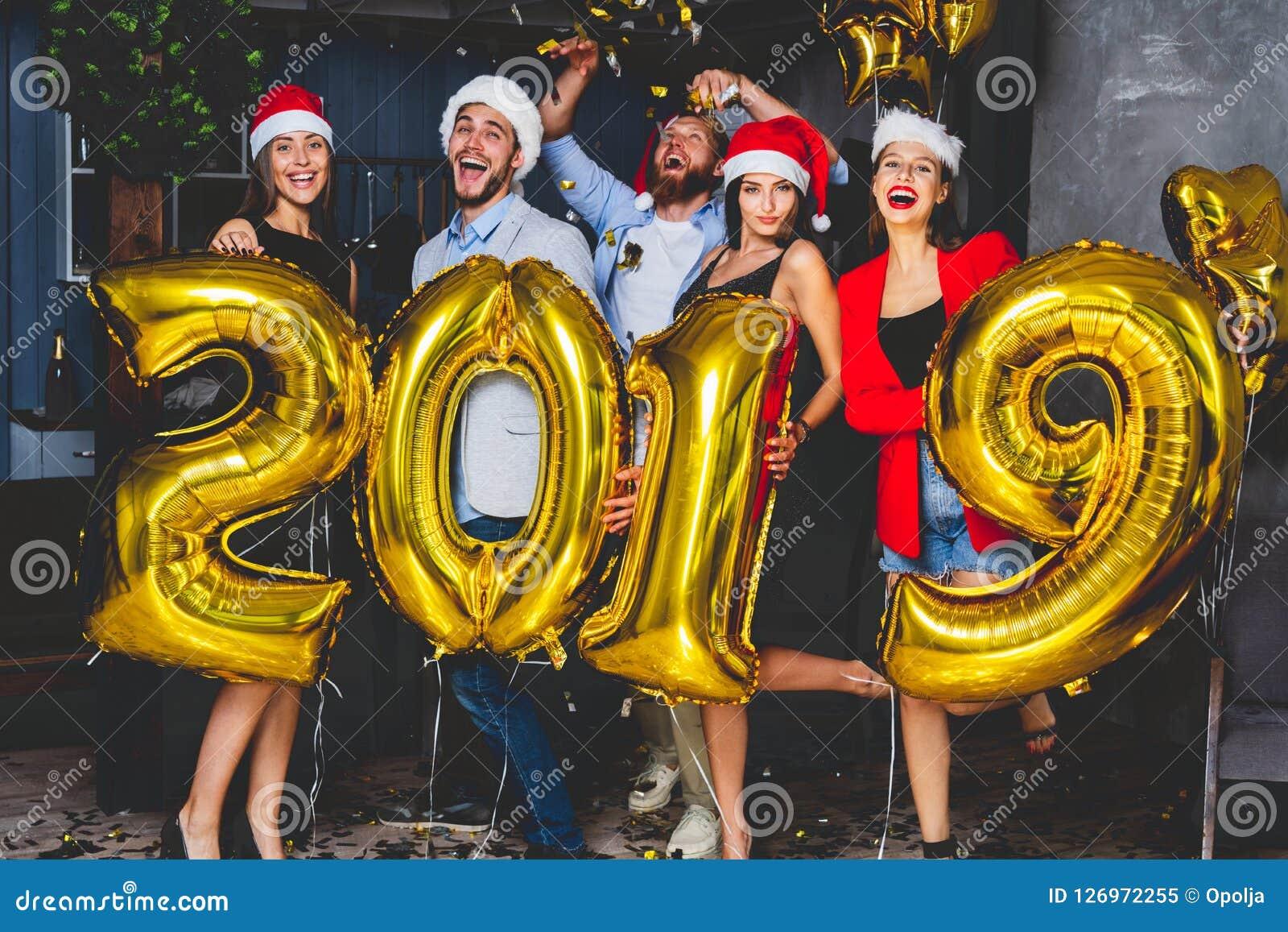 Vierende Nieuwjaarpartij De groep vrolijke jonge meisjes in mooi dragend dragend goud kleurde nummer 2019 en