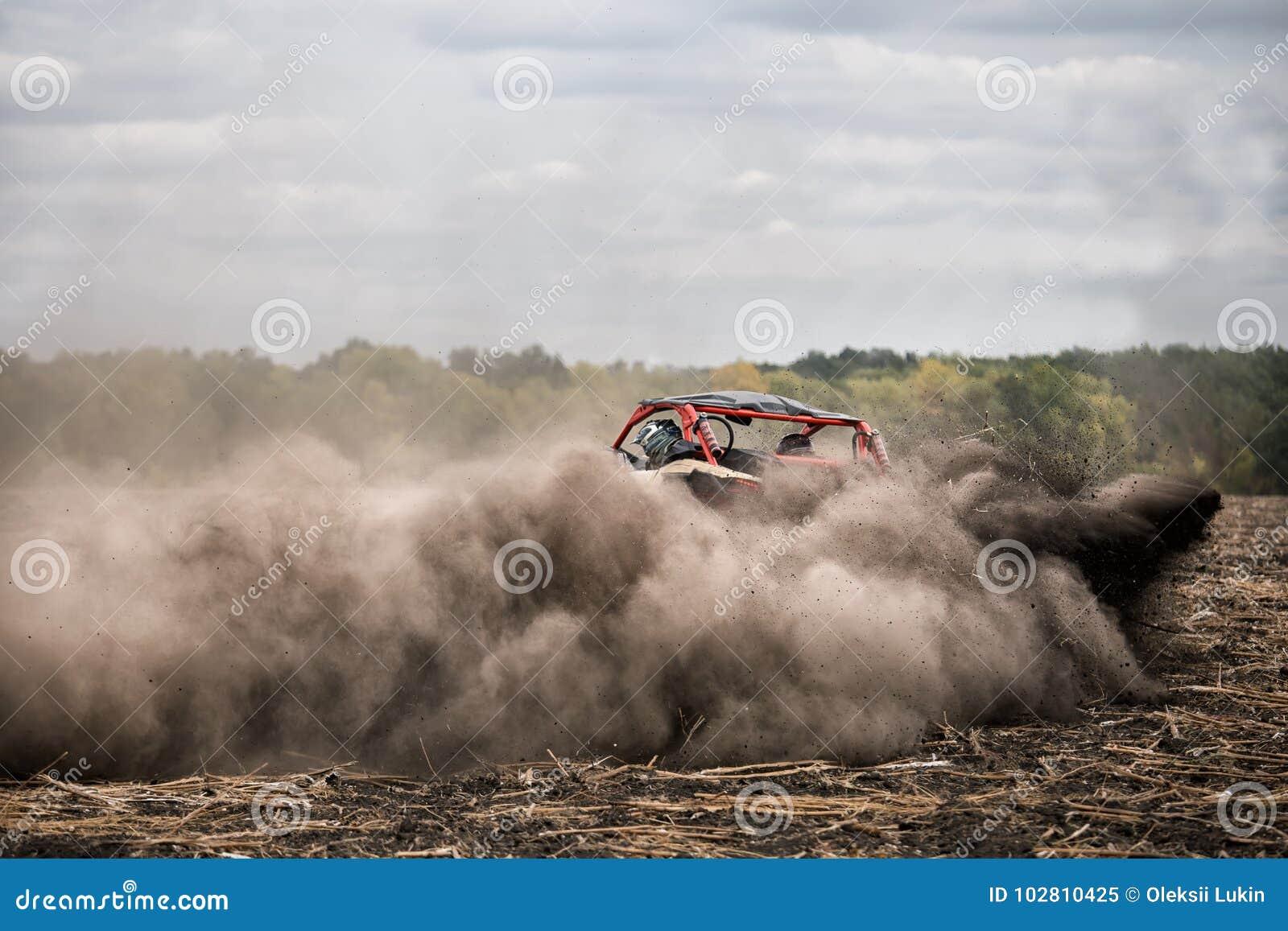 Viererkabelfahrrad mit Fahrer im Fahrerhaus hetzt durch Feld im Staub