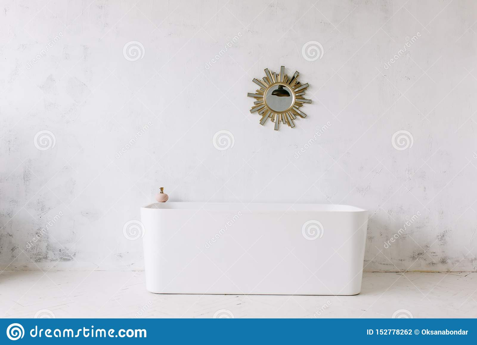 Vierkant kader van moderne badkamers met freestanding witte badkuip op achtergrond van de zolder de rustieke muur met de spiegel