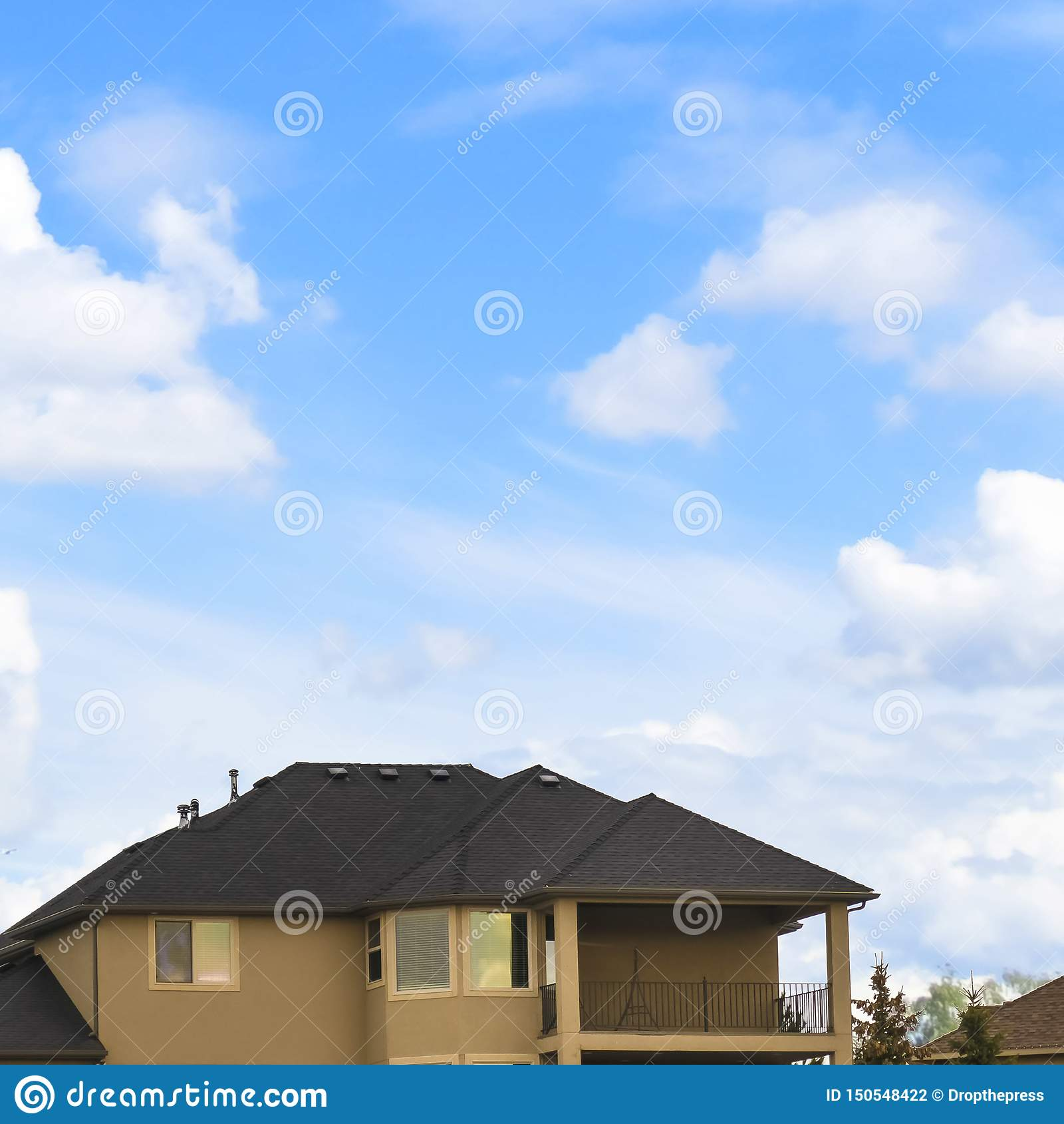 Vierkant kaderhuis Met drie verdiepingen met portiek en balkon tegen blauwe hemel met heldere wolken