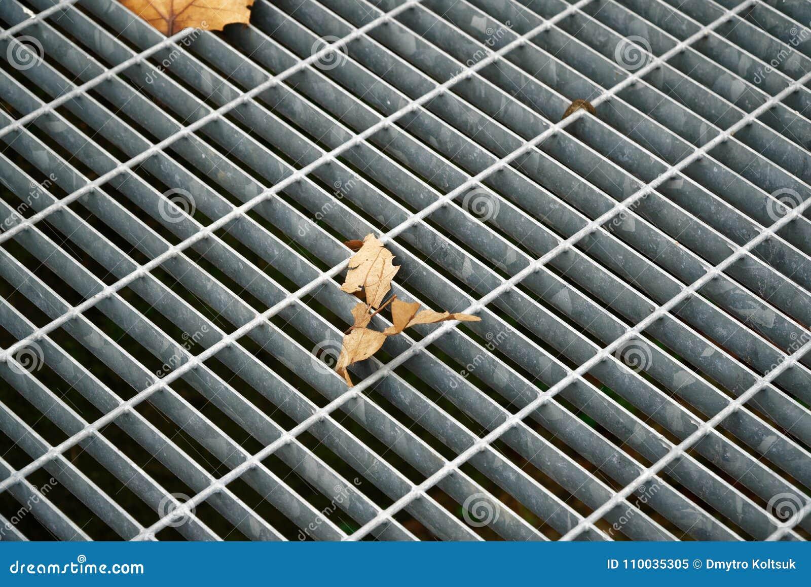 Vierkant metaalbroedsel in stedelijke bestrating, de dekking van het rioolmangat met binnen het merken van lijnen en blad