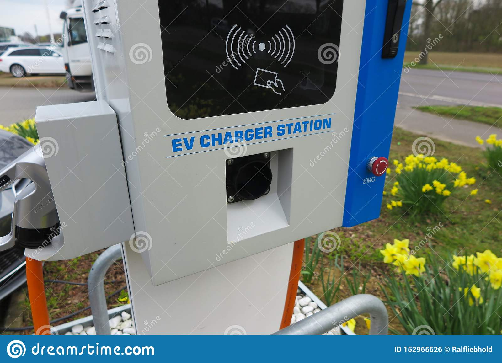 VIERSEN, GERMANY - MARCH 27. 2019: Close up of charging station for electric cars surrounded by yellow tulips