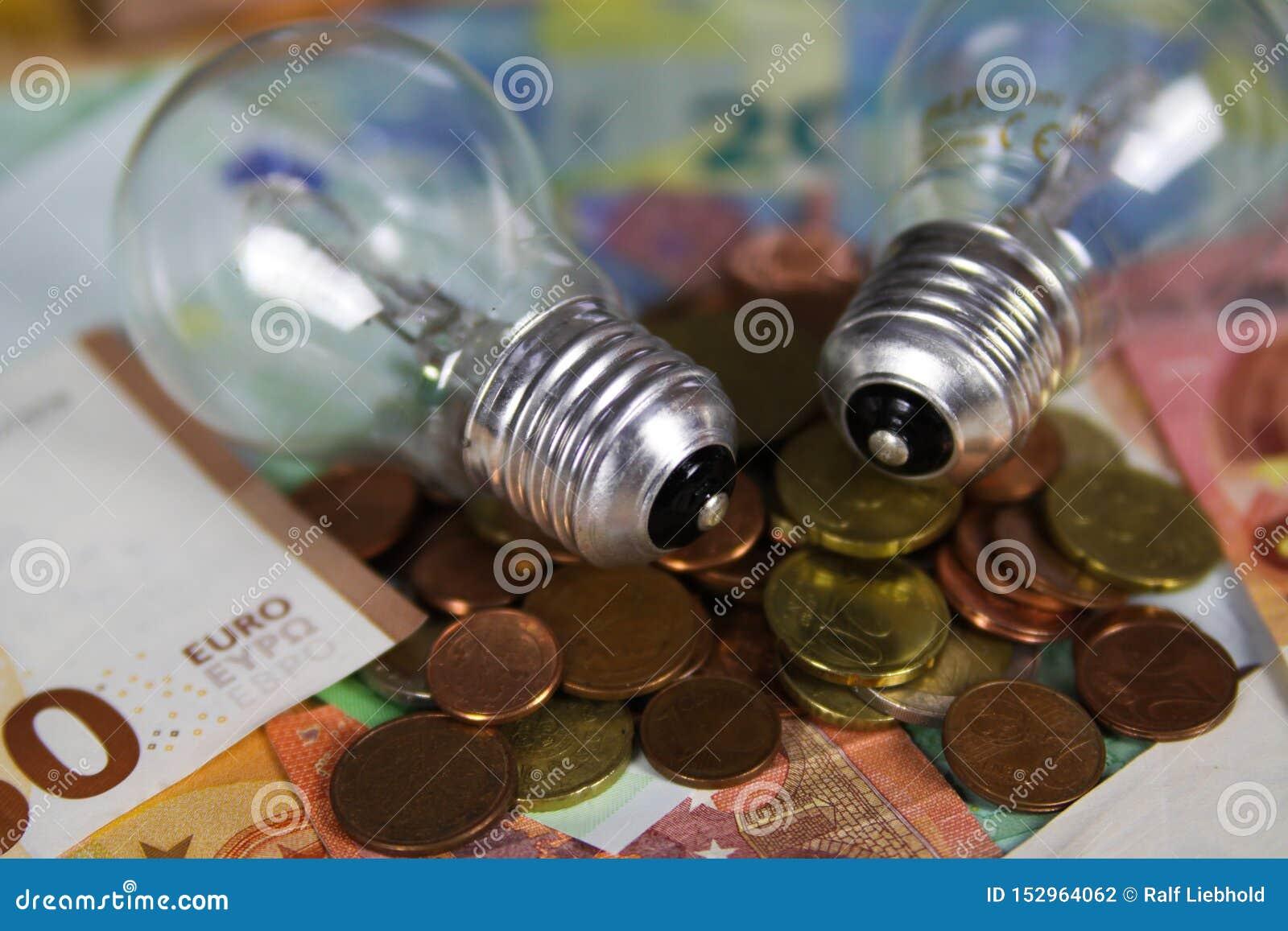VIERSEN NIEMCY, MAJ, - 20 2019: Źródło zasilania kosztu pojęcie Elektryczne żarówki na Euro papierowego pieniądze banknotach mone