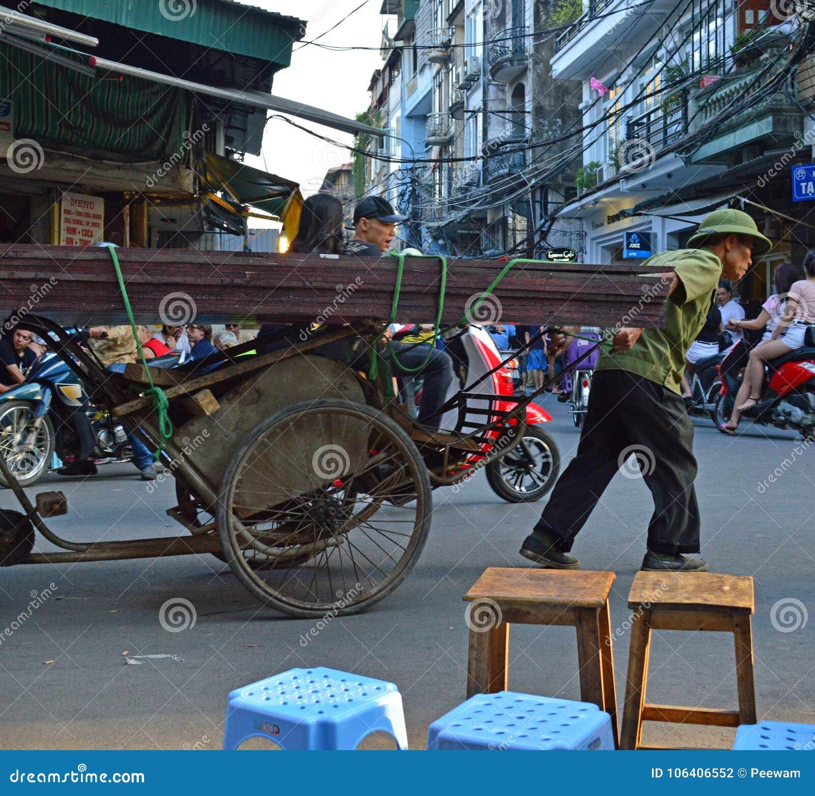 Vietnam - Hanoi - typical street scene from the Old Quarter - man pulling rickshaw full of metal
