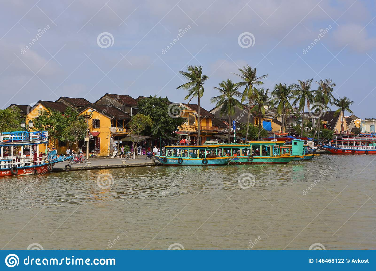 Vietname, Hoi An - em janeiro de 2017: Flutuadores do barco em Bon River contra o contexto das casas na margem na cidade de Hoi A