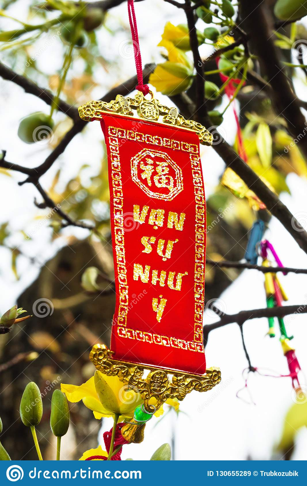 Vietnamese and Chinese New Year decoration on a background of yellow flowers. The inscription is translated - Great Consciousness
