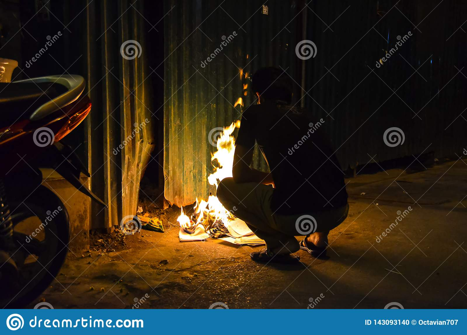 Vietnamese guy burning paper at night