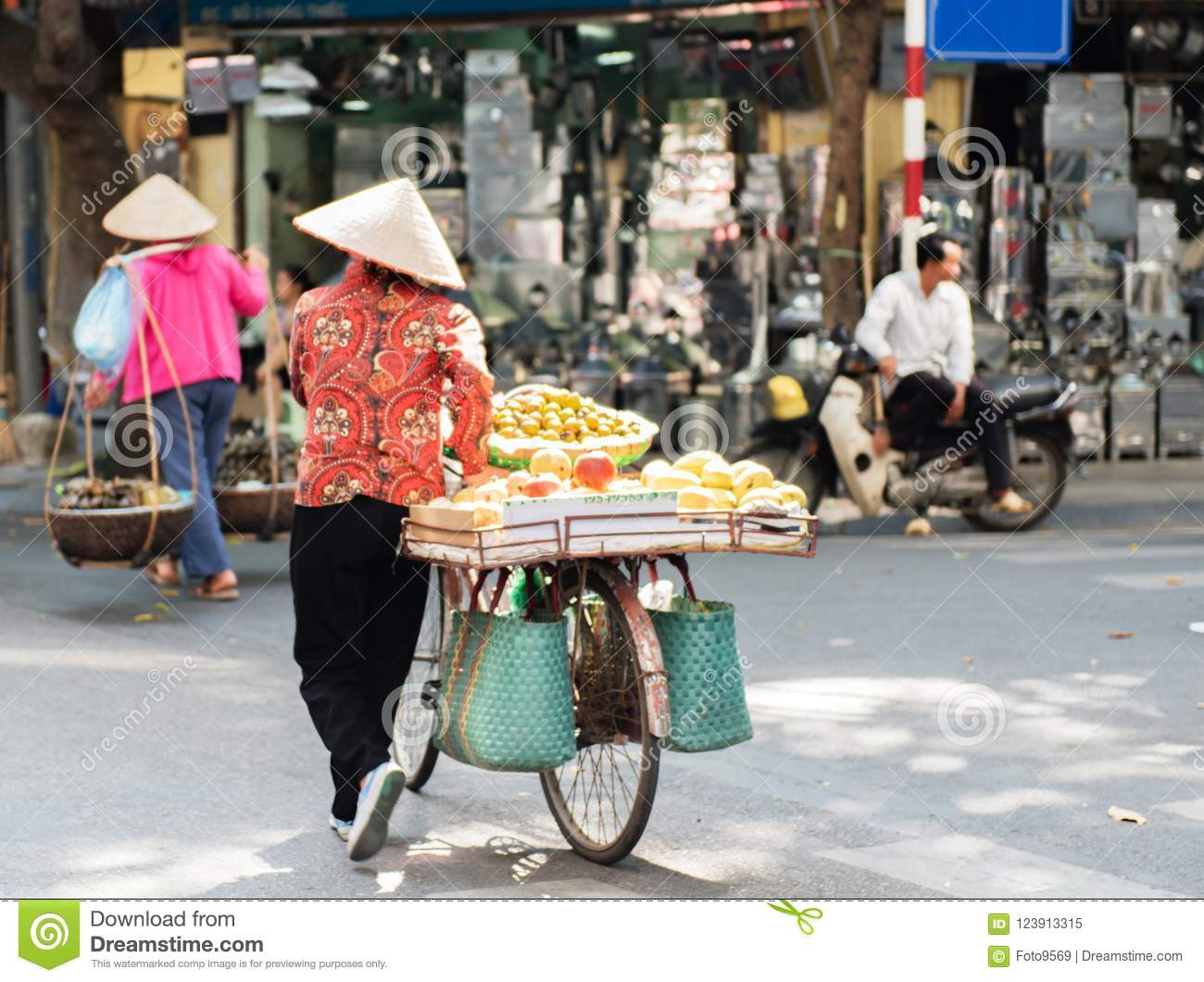 Vietnamese street vendors act and sell their vegetables and fruit products in Hanoi, Vietnam