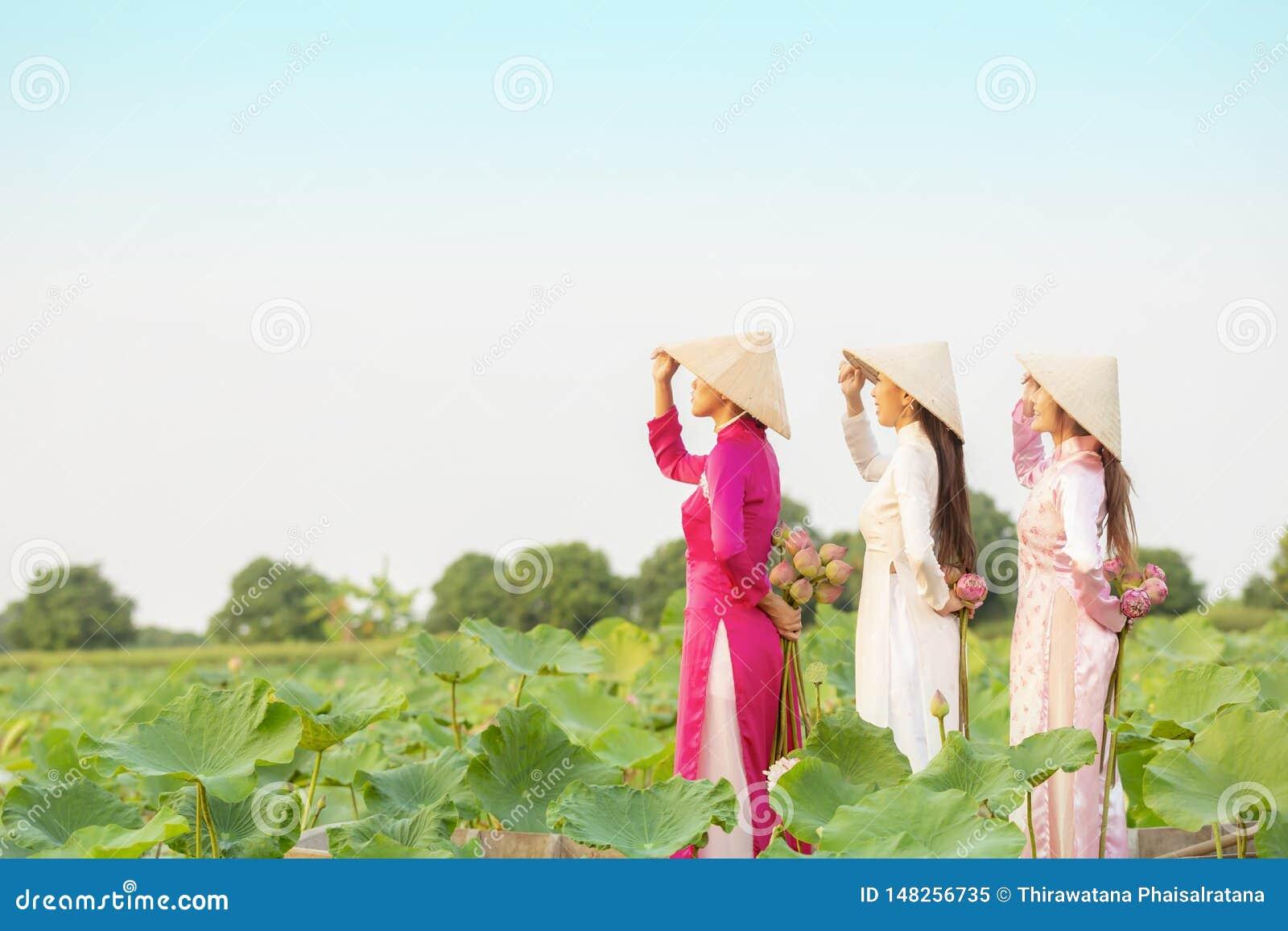 Vietnamesisk kvinnlig grupp på en träfartygasiat tre kvinnor står på träblommor för en lotusblomma för fartyg mot efterkrav h?rli