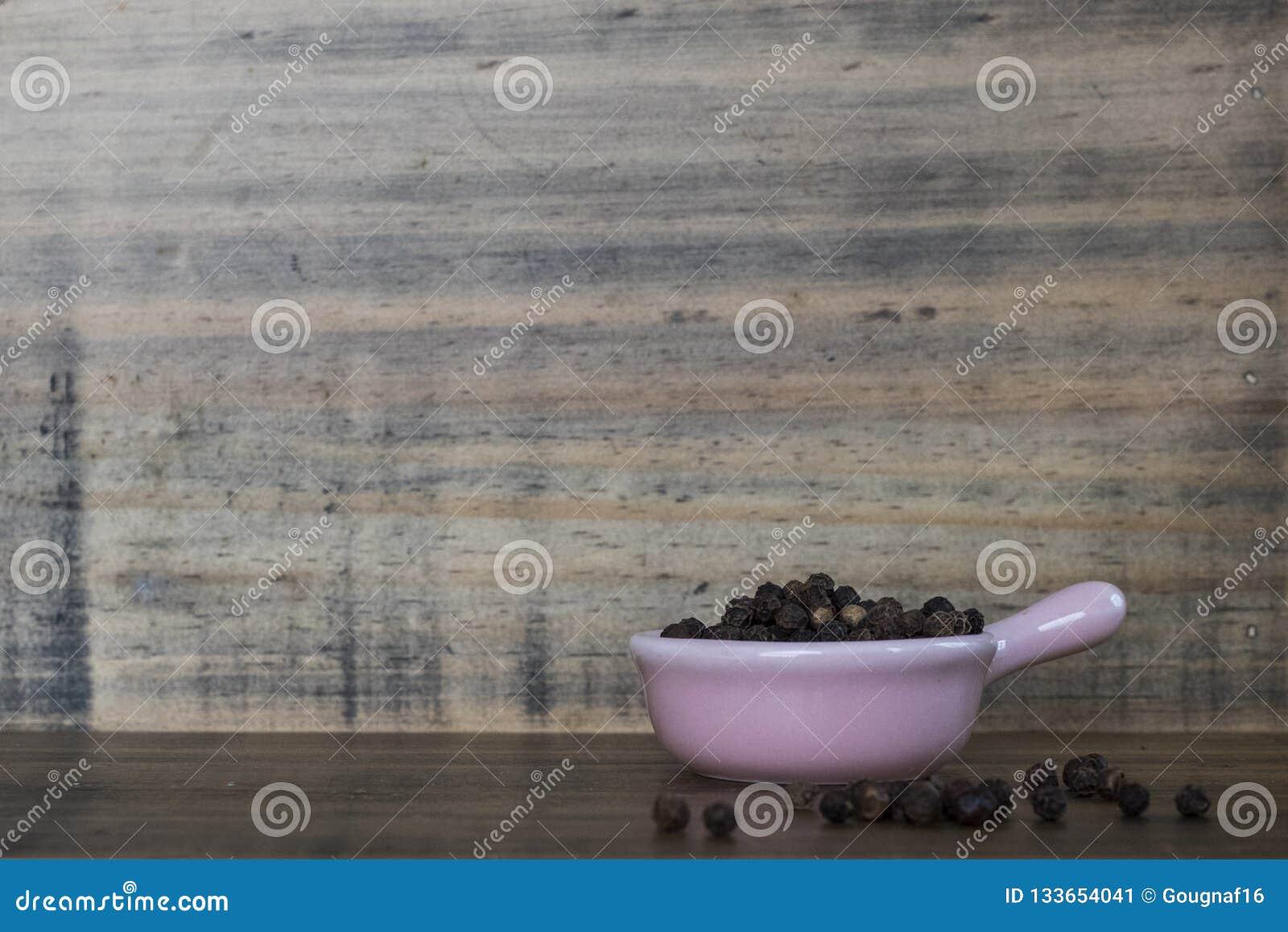 Vietnamita preto inteiro em um potenciômetro cerâmico cor-de-rosa diminuto em uma placa de madeira e em um fundo