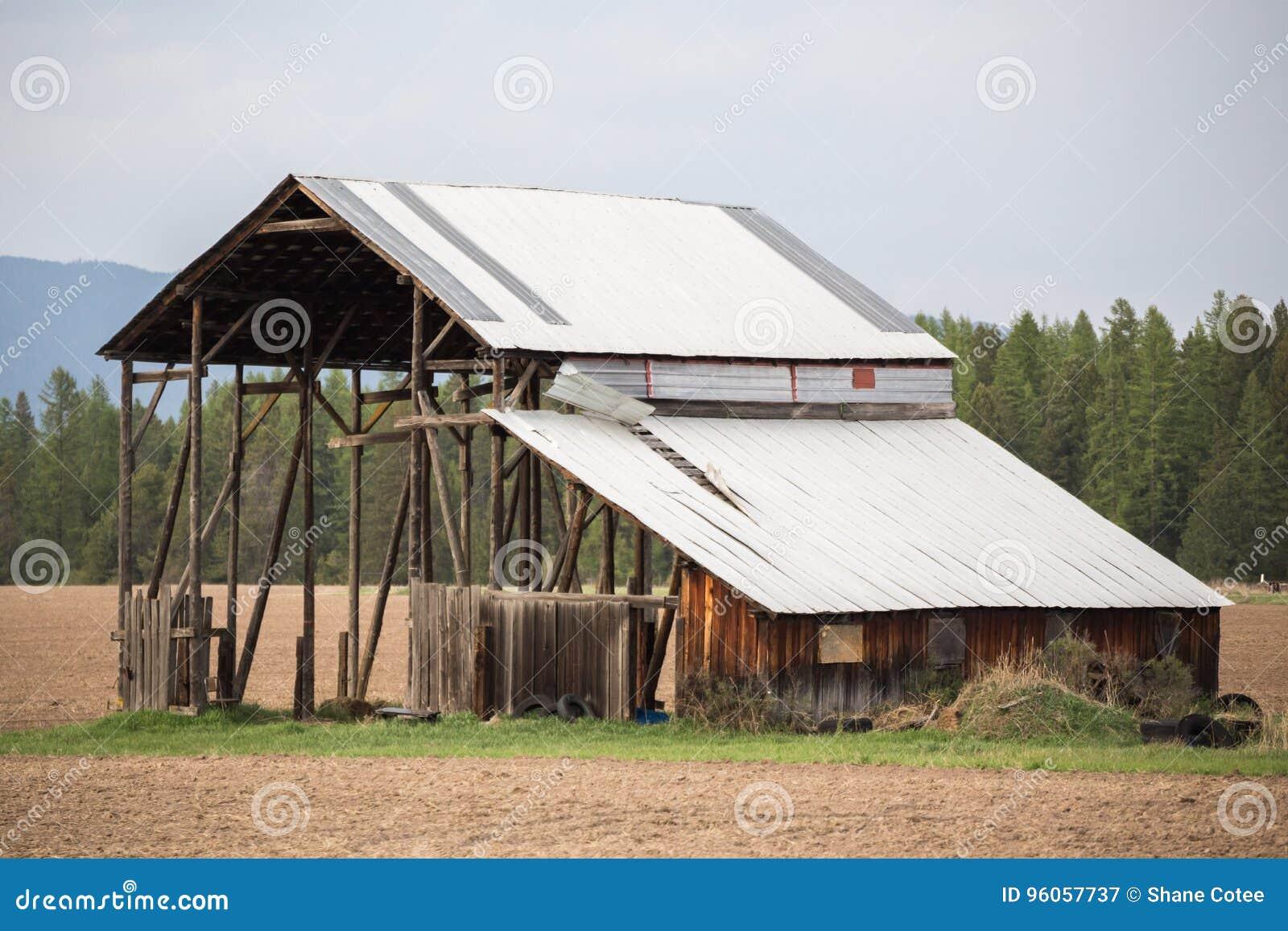 Vieux bâtiment de grange avec le toit ébouriffé par le vent