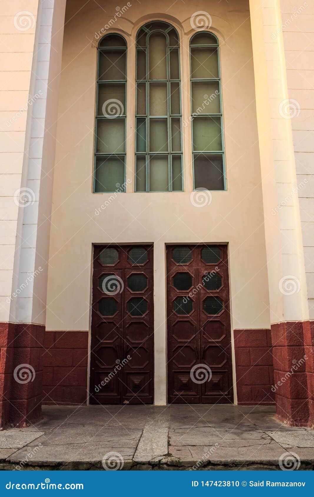 Vieux b?timent dans des couleurs beiges et marron avec de hautes fen?tres et portes