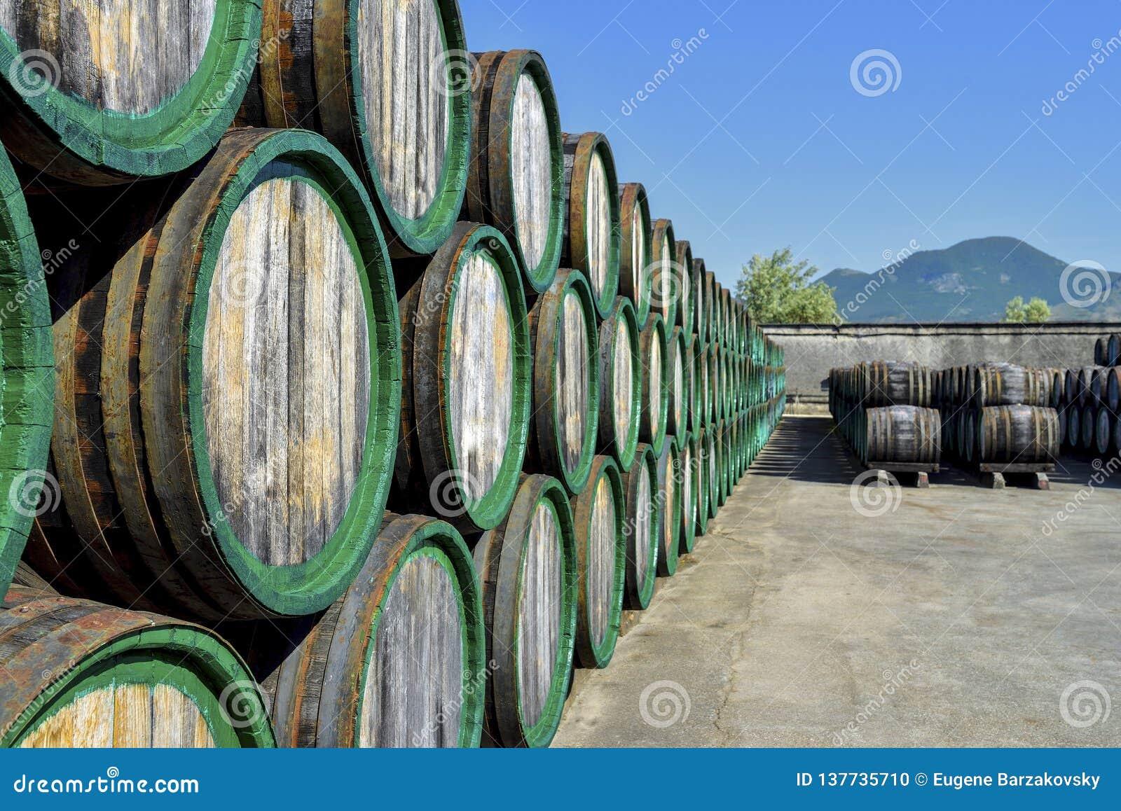 Vieux barils de vin en bois empilés en air ouvert