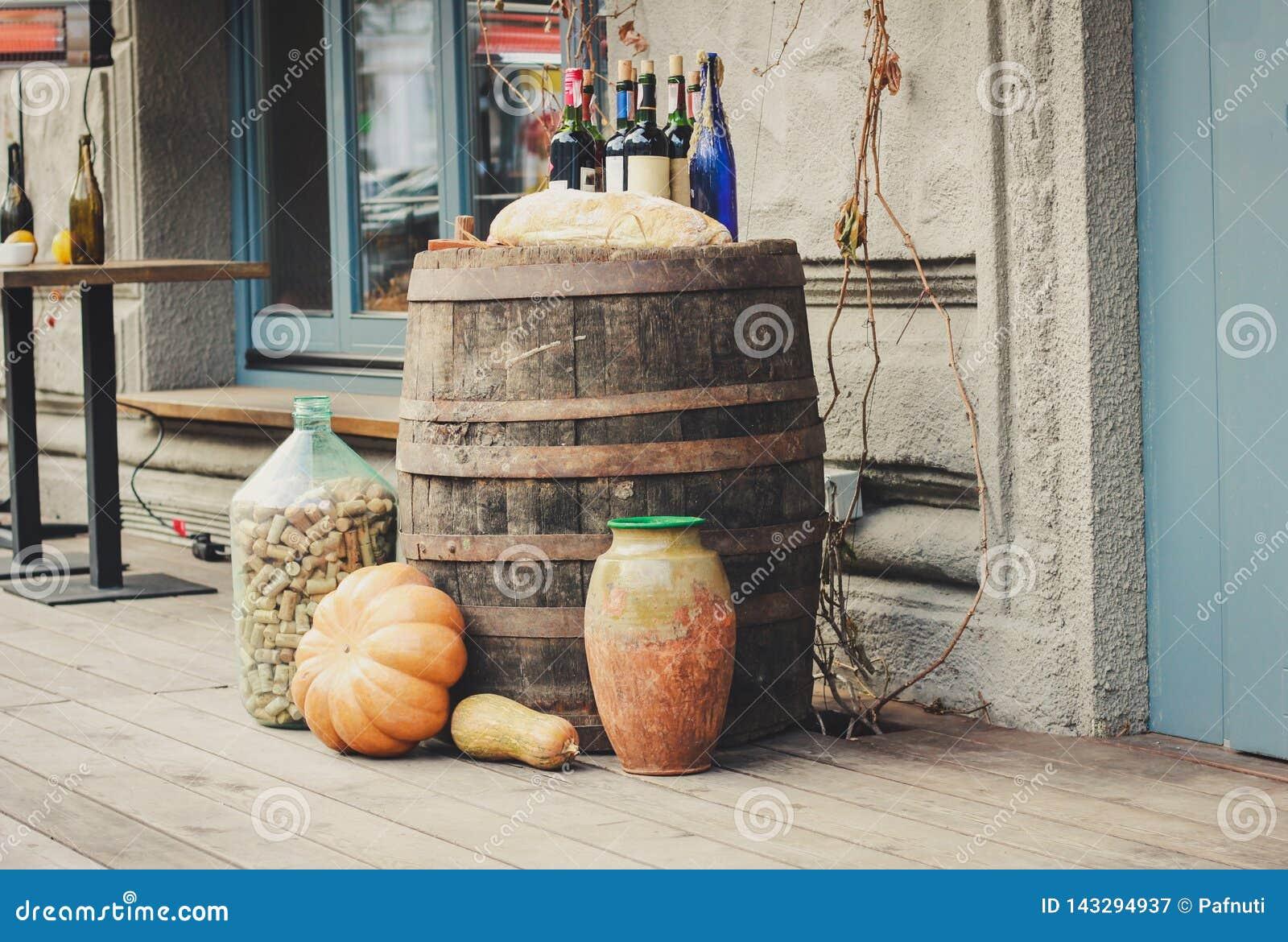 Vieux barils en bois sur lesquels il y a des potirons et des bouteilles