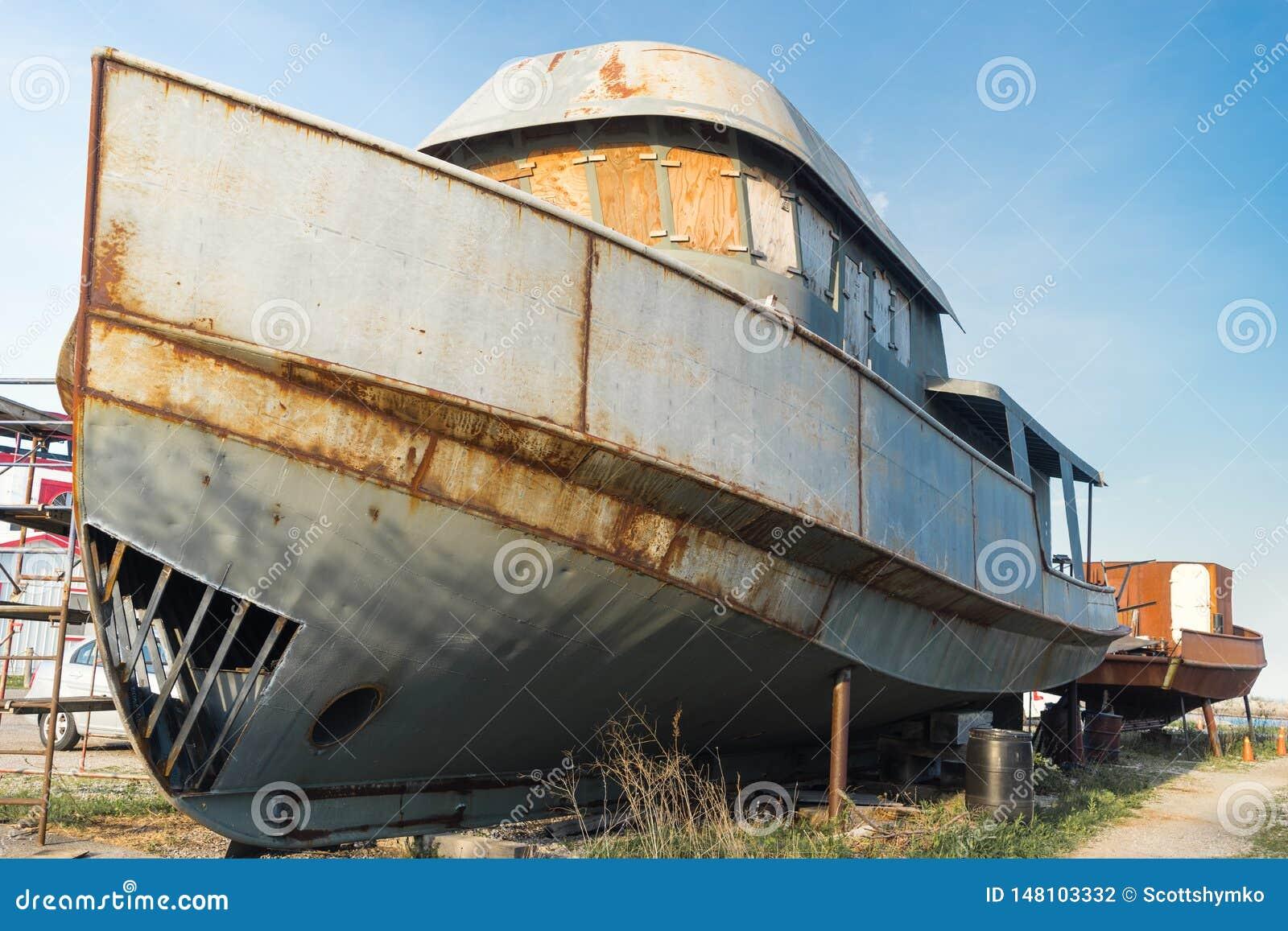Vieux bateaux de pêche sur la terre pour la réparation