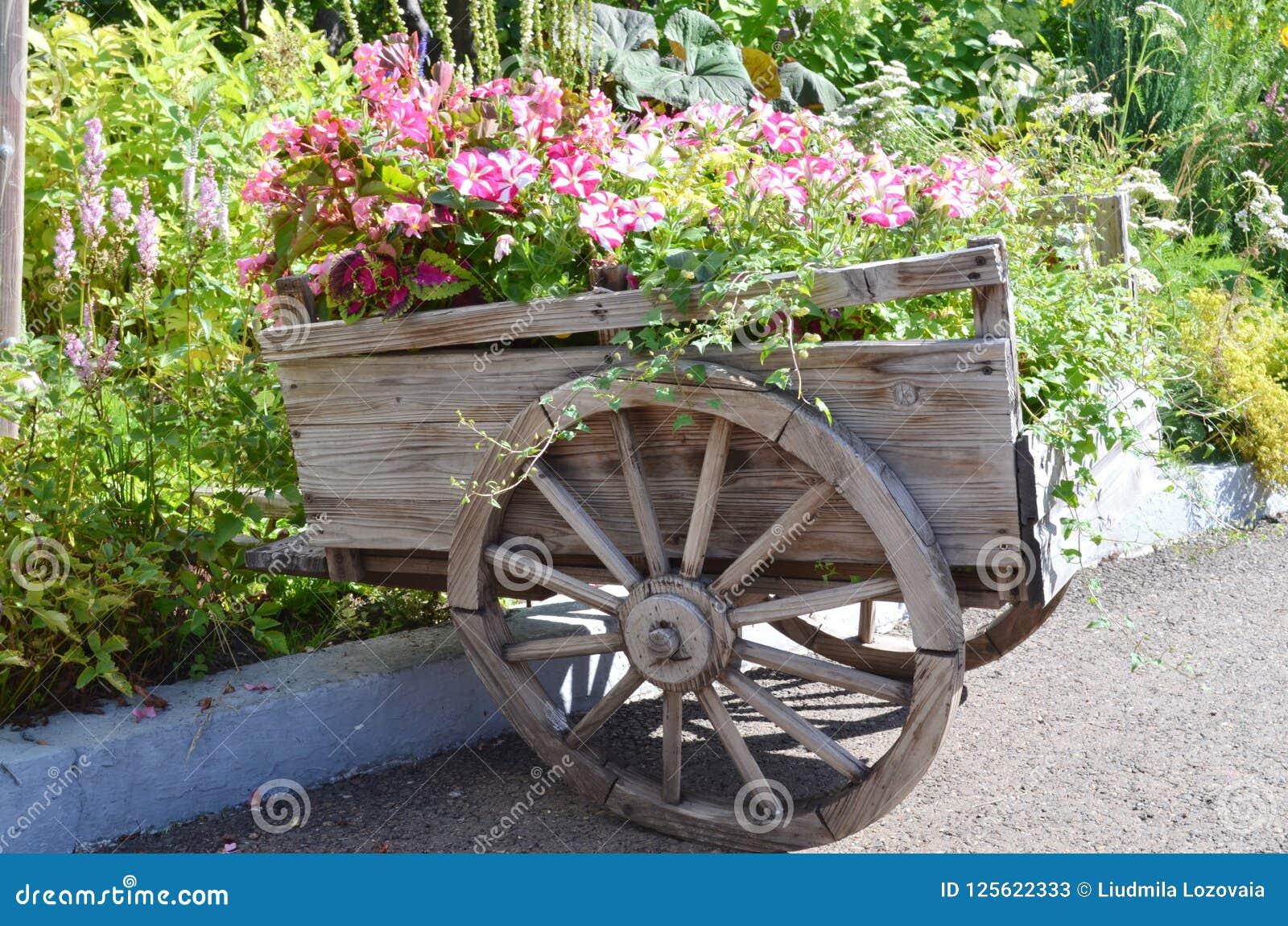 Vieux chariot en bois avec des fleurs