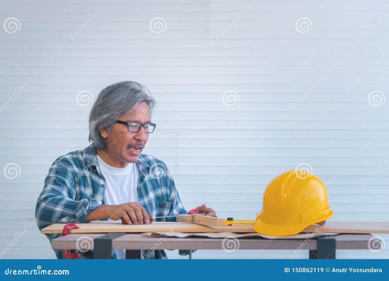 Vieux constructeur avec des outils et plan de papier sur la table de fonctionnement