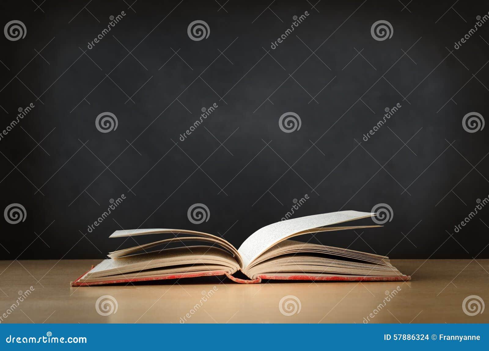 vieux livre ouvert sur le bureau avec le tableau l 39 arri re plan photo stock image 57886324. Black Bedroom Furniture Sets. Home Design Ideas