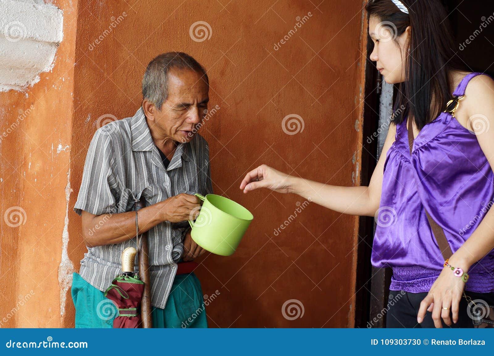 Vieux mendiant masculin aveugle tenant le plongeur de l eau recevant l aumône d une femme aux ruines portailes d église