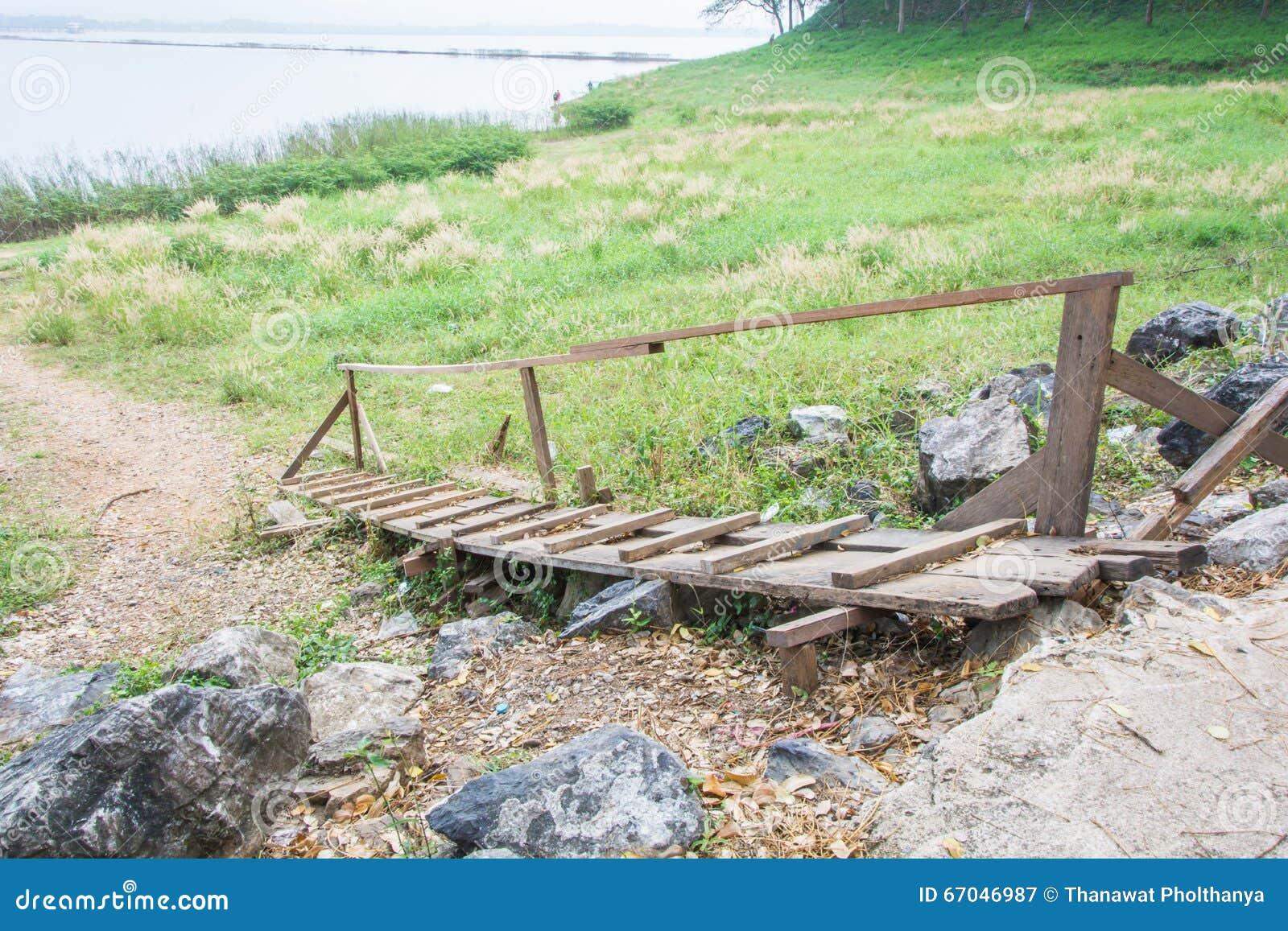 Vieux pont en bois vers le bas à l herbe de champ près du reservior