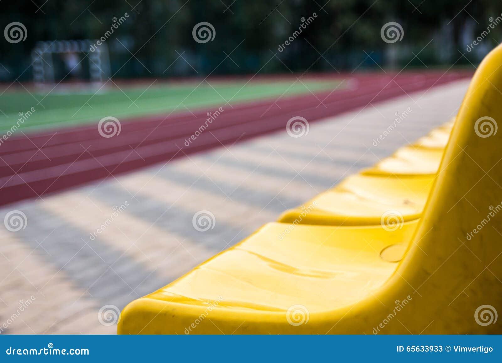 Vieux sièges jaunes dans le stade Fond de sport
