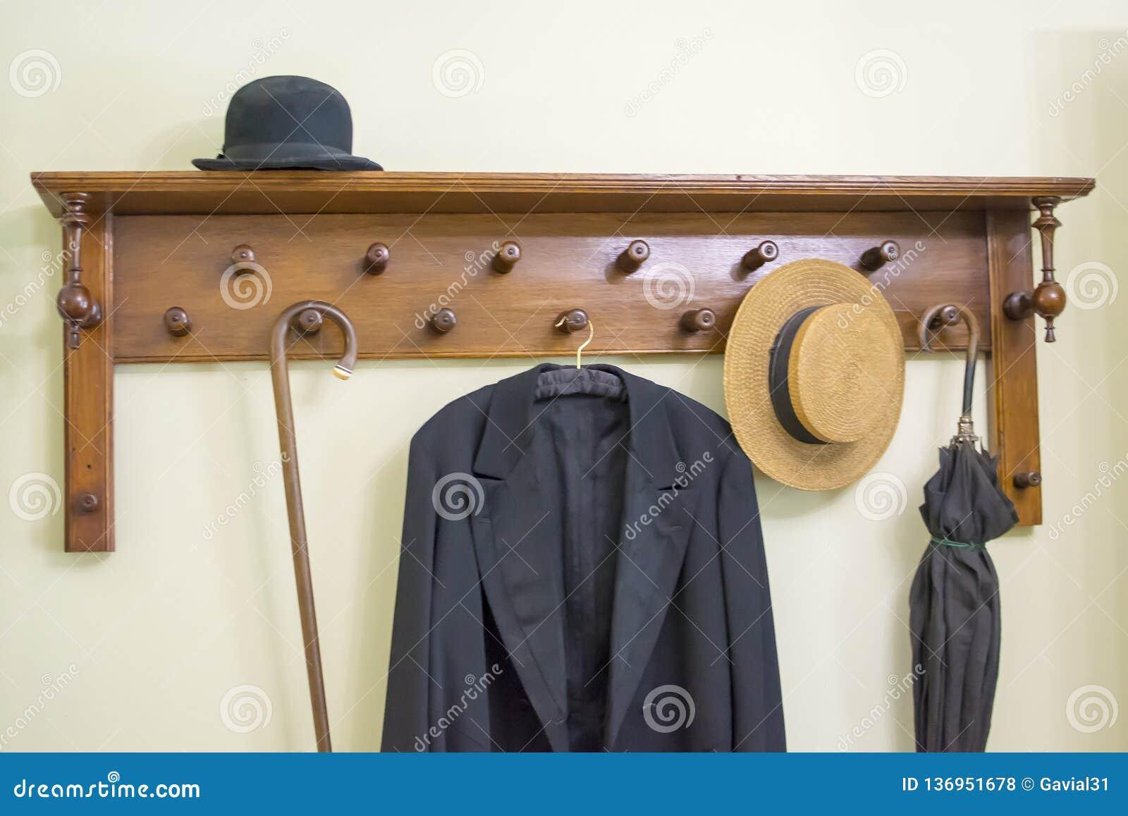 Vieux support de manteau avec le parapluie, le chapeau et le manteau