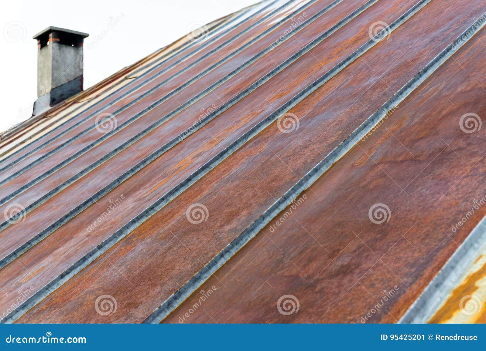 Vieux toit rouillé en métal de fer avec la cheminée