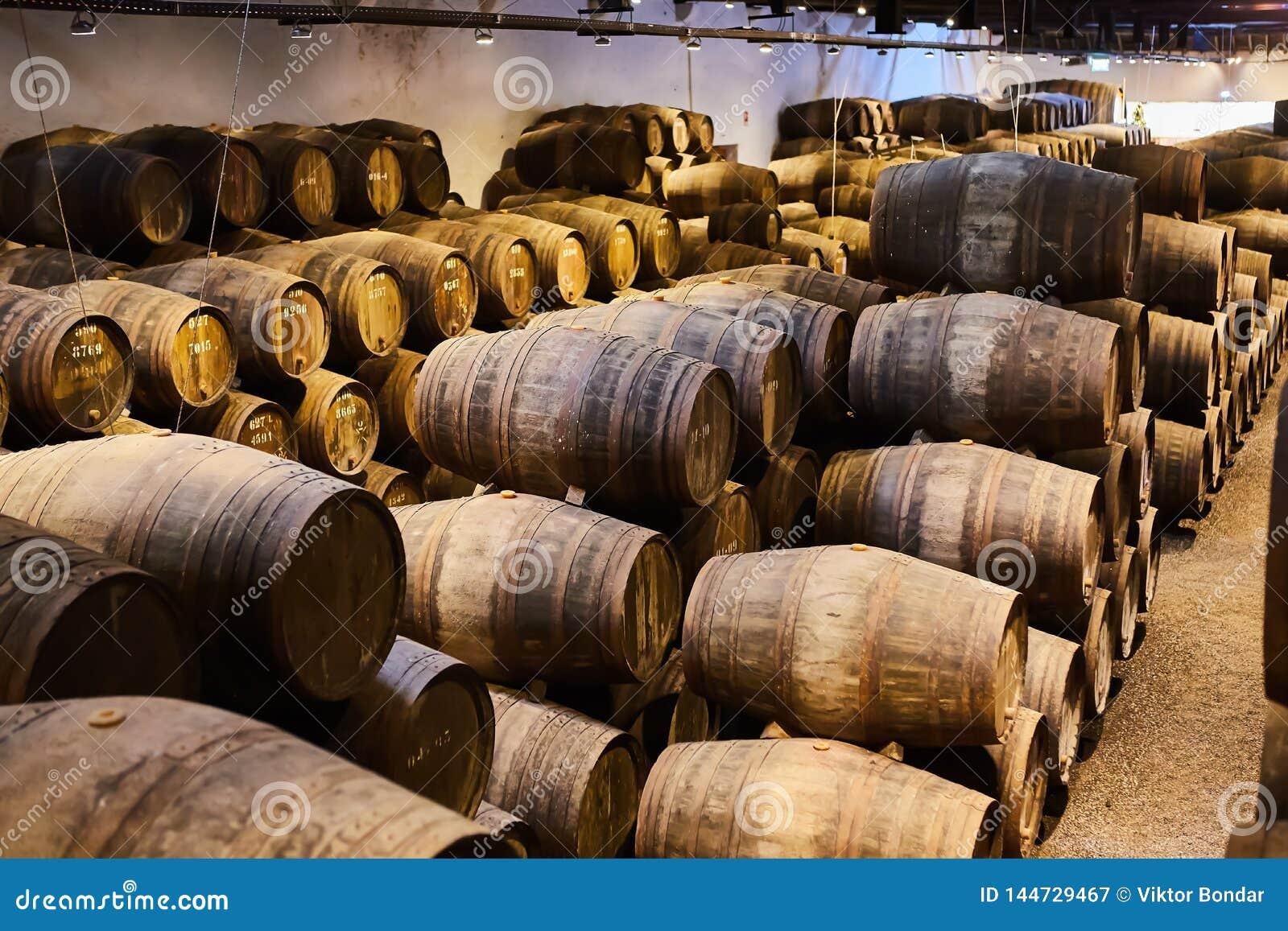 Vieux a vieilli les barils en bois traditionnels avec du vin dans une chambre forte align?e dans la cave fra?che et fonc?e en Ita