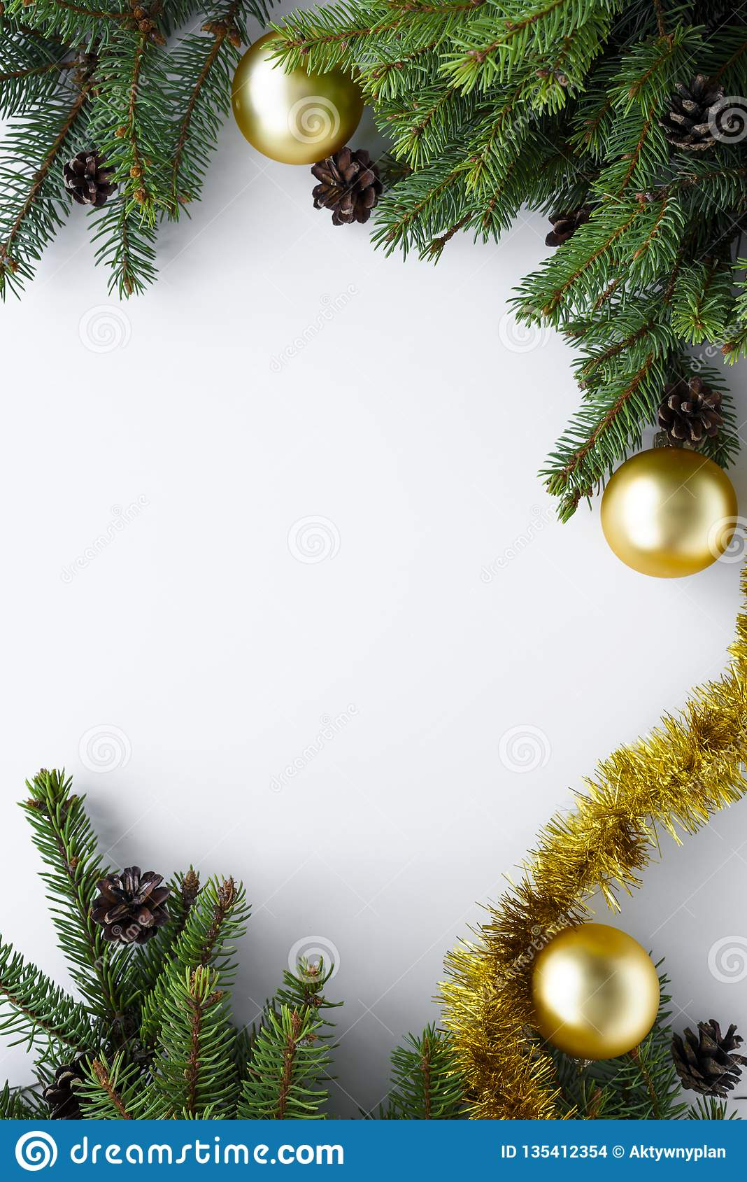 View from above on white table with christmas decoration in a vertical frame with copy space. Spruce branches and ornaments like