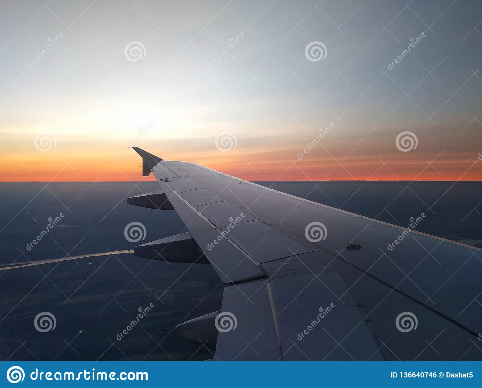 View from airplane window to beautiful sunrise or sunset. Wing of plane flying above in the sky