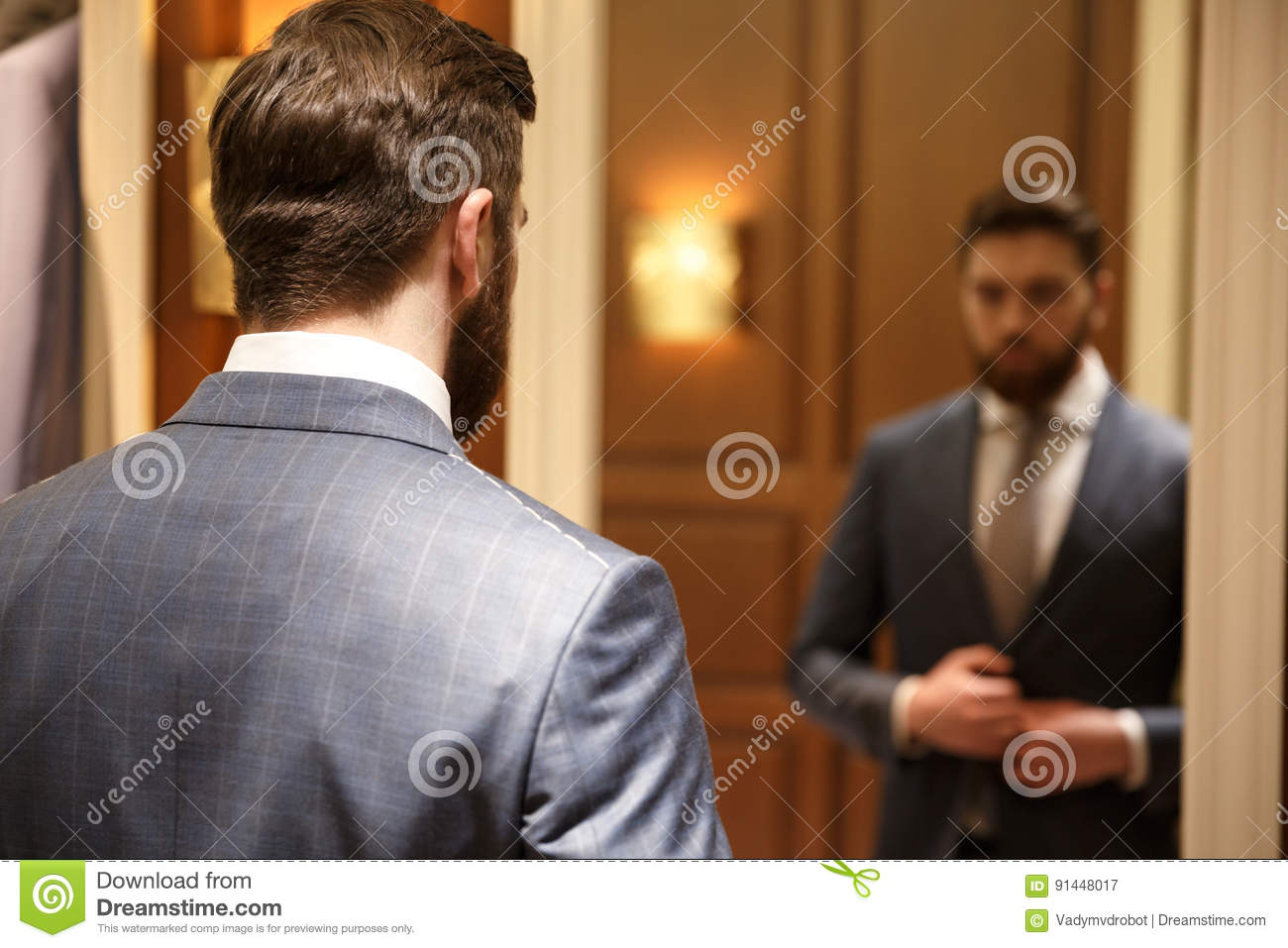 view from back of bearded man looking at the mirror stock