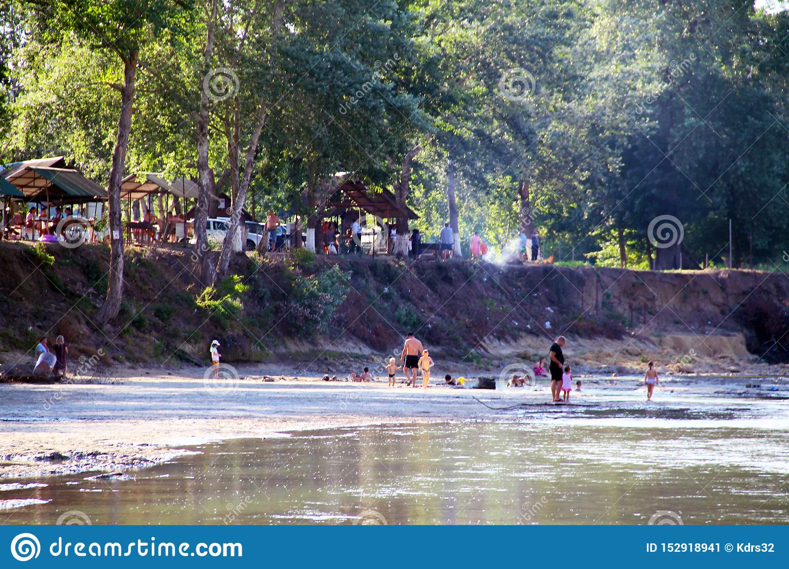 View of the Belaya River and the public park along the river. People relax on the river bank
