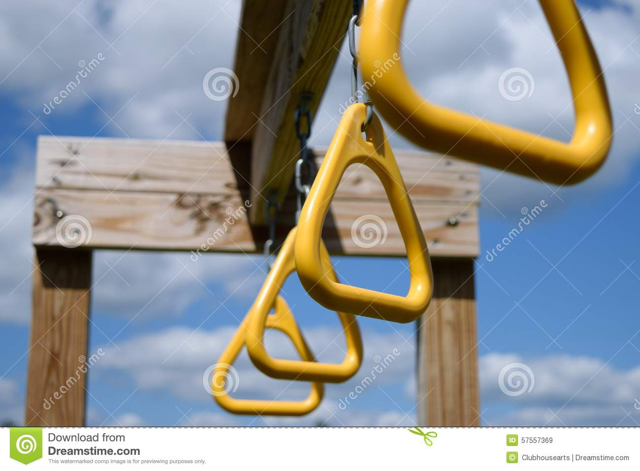 View from below of monkey bar rings hanging from wooden beam stock