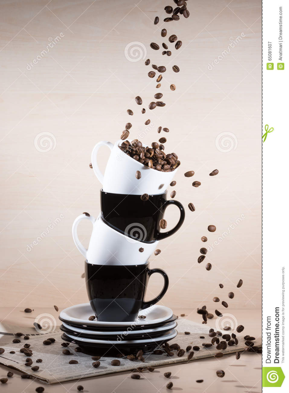 View of black and white cups on the stack of the plates with falling down brown roasted coffee beans on newspaper.