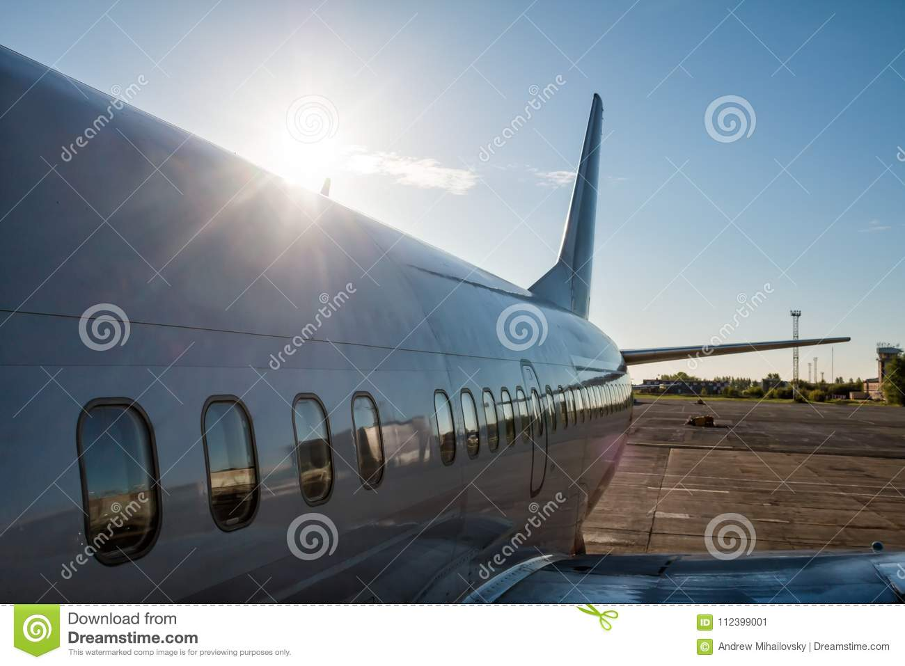 View from the boarding steps to the rear of the passenger plane in the rays of the rising sun
