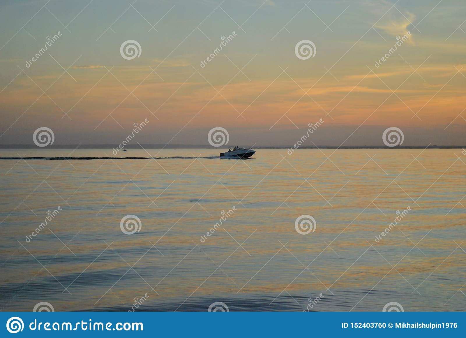 View of the boat floating on the surface of the Volga River against the sunset sky.
