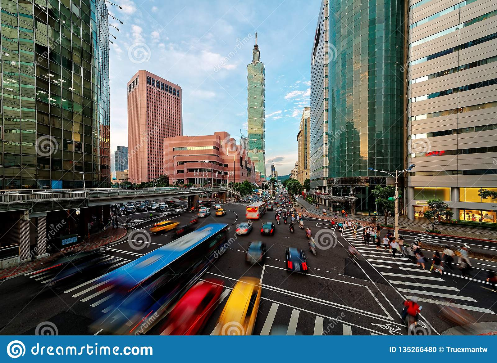 View of a busy street corner in Downtown Taipei City at rush hour with cars & buses dashing by