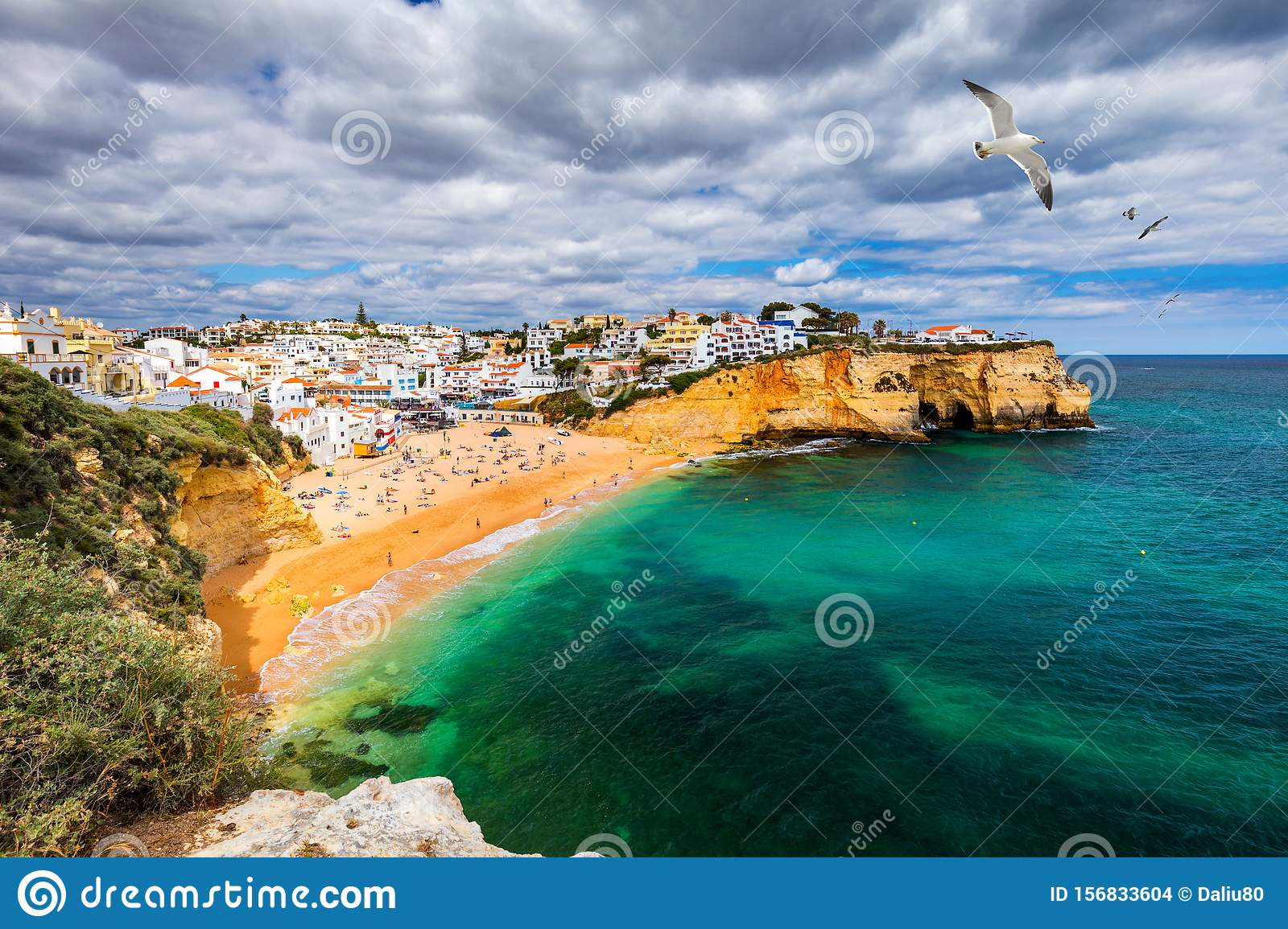 View of Carvoeiro fishing village with beautiful beach, Algarve, Portugal. View of beach in Carvoeiro town with colorful houses on